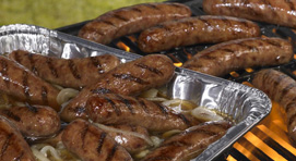Bratwurst in a foil pan and bratwursts on a flame grill