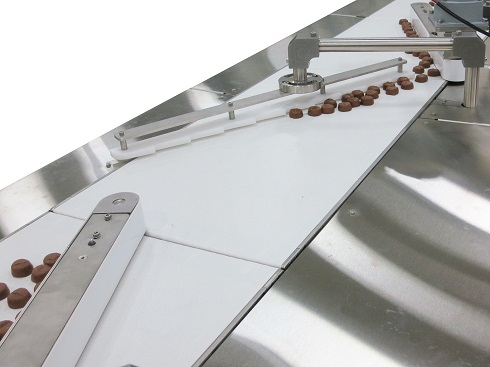 chocolates move on conveyor with sawtooth piece of UHMW