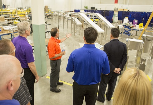 Dorner employee guiding tour of professional and showcasing conveyor belts